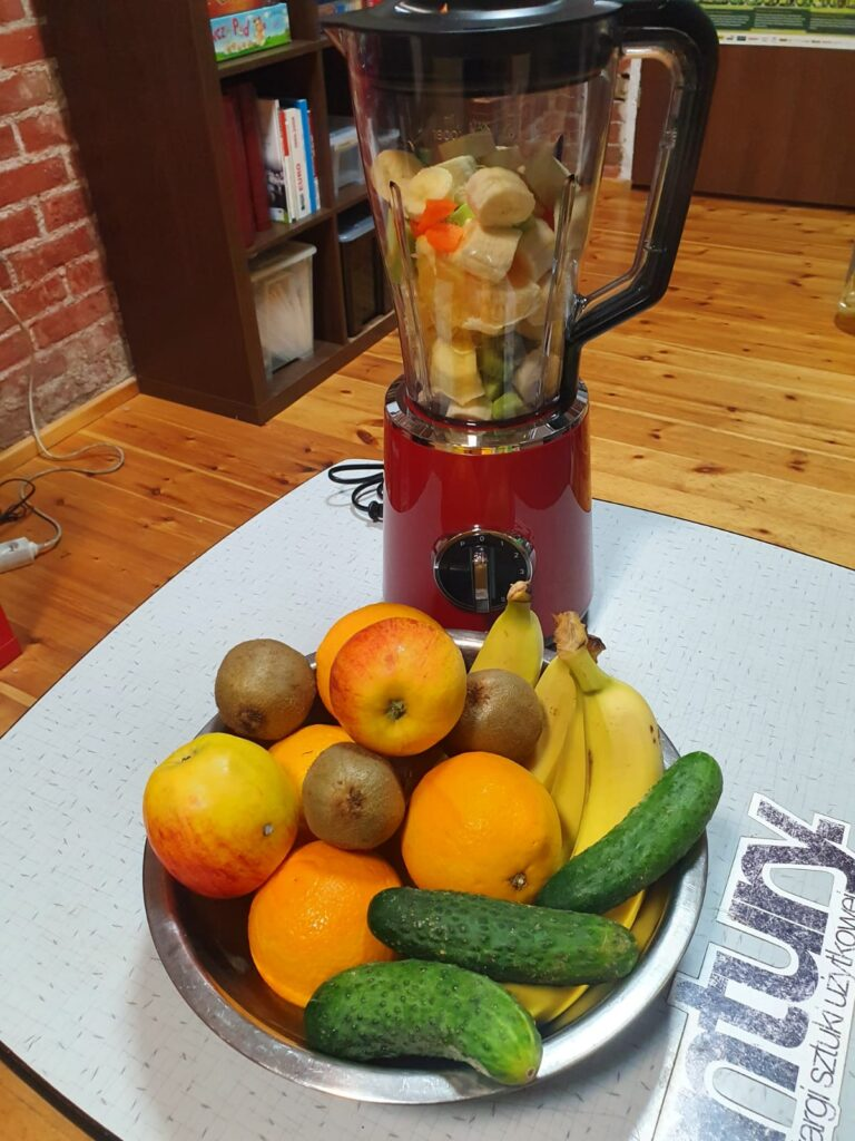 Na stole talerz owoców i warzyw. Za nimi blender.