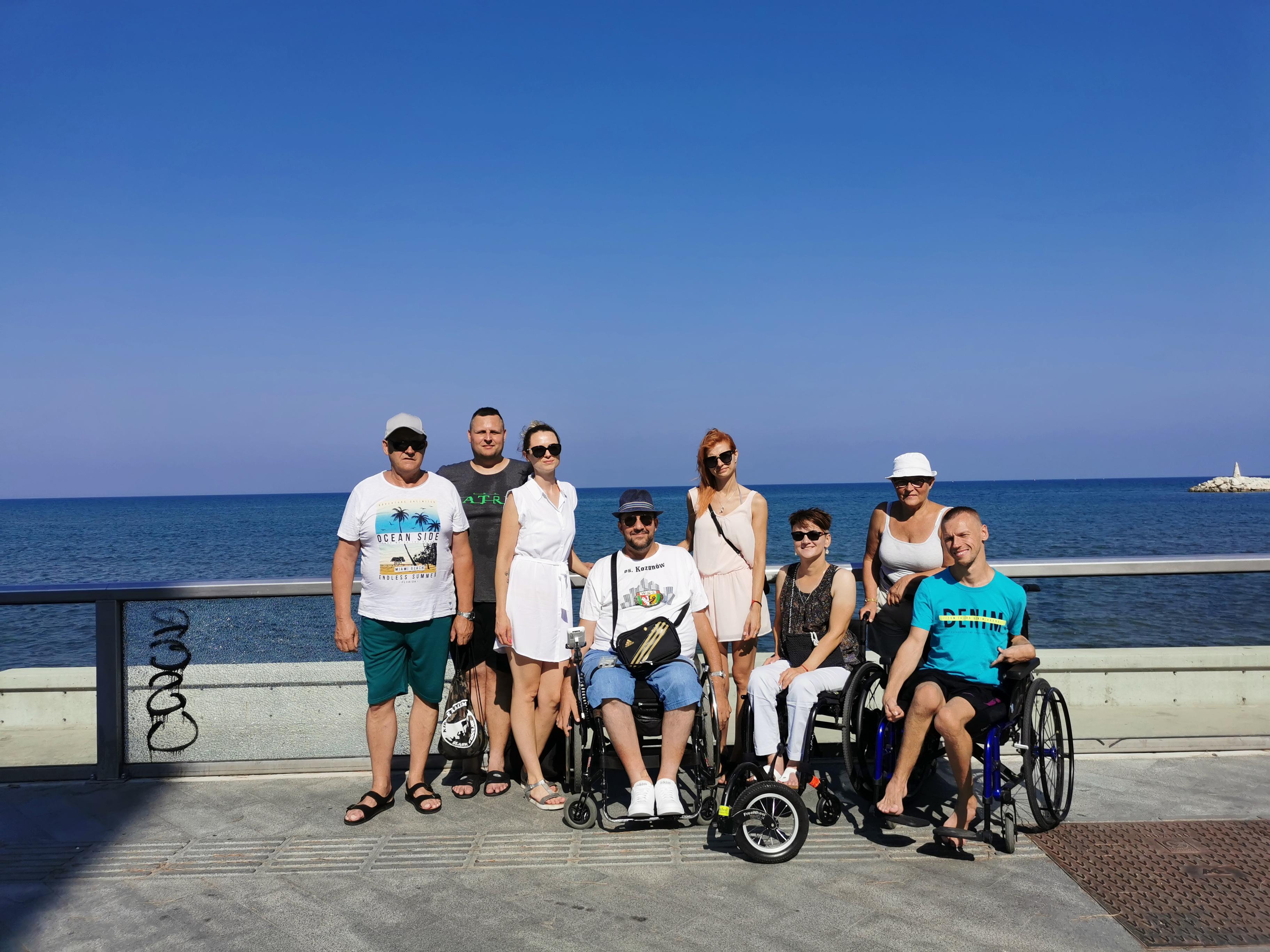 8 osób, w tym 3 na wózku, w wakacyjnym anturażu na tle morza.